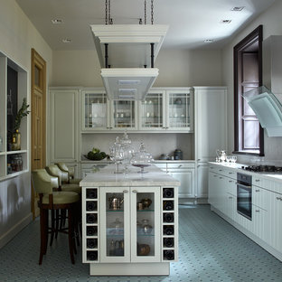 Klassisk inredning av ett avskilt vit vitt l-kök, med vita skåp, grått stänkskydd, svarta vitvaror, en köksö och turkost golv