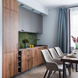 Пример оригинального дизайна: линейная кухня среднего размера в современном стиле с обеденным столом, полом из керамогранита, серым полом, врезной раковиной, плоскими фасадами, столешницей из ламината, зеленым фартуком, фартуком из керамической плитки, черной техникой, коричневой столешницей и фасадами цвета дерева среднего тона без острова