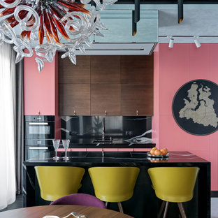 Photo of an eclectic galley eat-in kitchen in Saint Petersburg with an undermount sink, flat-panel cabinets, pink cabinets, black splashback, stone slab splashback, black appliances, with island, white floor and black benchtop.