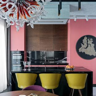 Пример оригинального дизайна: параллельная кухня в стиле фьюжн с обеденным столом, врезной раковиной, плоскими фасадами, розовыми фасадами, черным фартуком, фартуком из каменной плиты, черной техникой, островом, белым полом и черной столешницей