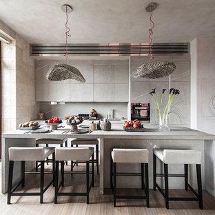 Неиссякаемый источник вдохновения для домашнего уюта: параллельная кухня-гостиная в современном стиле с плоскими фасадами, серыми фасадами, серым фартуком, фартуком из каменной плиты, островом, бежевым полом, монолитной раковиной, столешницей из гранита, техникой из нержавеющей стали и светлым паркетным полом