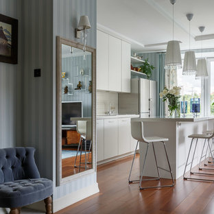 Contemporary single-wall open plan kitchen in Moscow with flat-panel cabinets, white cabinets, white splashback, medium hardwood floors, with island and brown floor.