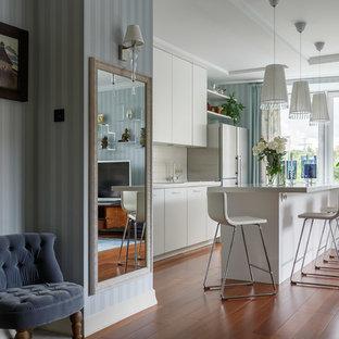 На фото: прямая кухня-гостиная в современном стиле с плоскими фасадами, белыми фасадами, белым фартуком, паркетным полом среднего тона, островом и коричневым полом с