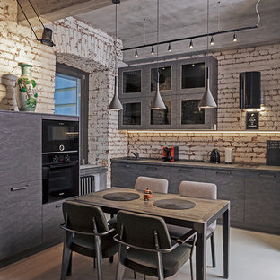 На фото: угловая кухня-гостиная среднего размера в стиле лофт с плоскими фасадами, серыми фасадами, столешницей из акрилового камня, фартуком из кирпича, черной техникой и светлым паркетным полом без острова с
