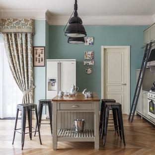Стильный дизайн: прямая кухня в стиле кантри с серыми фасадами, серым фартуком, фартуком из каменной плиты, белой техникой, светлым паркетным полом, островом, бежевым полом, фасадами с утопленной филенкой и деревянной столешницей - последний тренд