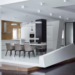 Пример оригинального дизайна: угловая кухня в современном стиле с плоскими фасадами, белыми фасадами, коричневым фартуком, техникой из нержавеющей стали, полуостровом, белым полом и белой столешницей