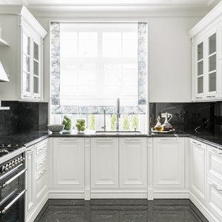 Неиссякаемый источник вдохновения для домашнего уюта: п-образная кухня в классическом стиле с врезной раковиной, фасадами с выступающей филенкой, белыми фасадами, черным фартуком, фартуком из каменной плиты, техникой из нержавеющей стали, черным полом и черной столешницей