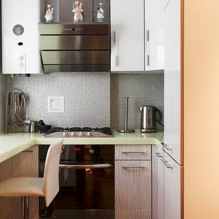 Moderne Küche in L-Form mit flächenbündigen Schrankfronten, Küchenrückwand in Grau, schwarzen Elektrogeräten, grüner Arbeitsplatte, weißen Schränken, Mineralwerkstoff-Arbeitsplatte, Rückwand aus Mosaikfliesen, Unterbauwaschbecken und grauem Boden in Moskau