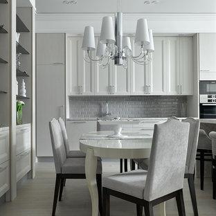 Пример оригинального дизайна: прямая кухня в стиле неоклассика (современная классика) с обеденным столом, фасадами с утопленной филенкой, серым фартуком, фартуком из плитки кабанчик, светлым паркетным полом, серой столешницей, белыми фасадами и серым полом