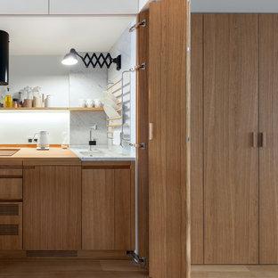 Стильный дизайн: маленькая прямая кухня в современном стиле с врезной раковиной, фасадами цвета дерева среднего тона, деревянной столешницей, белым фартуком, техникой под мебельный фасад, паркетным полом среднего тона, плоскими фасадами и коричневым полом без острова - последний тренд