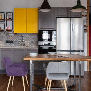 Immagine di una cucina industriale con lavello sottopiano, ante in stile shaker, ante in legno bruno, paraspruzzi grigio, elettrodomestici in acciaio inossidabile, parquet scuro, pavimento marrone e top beige