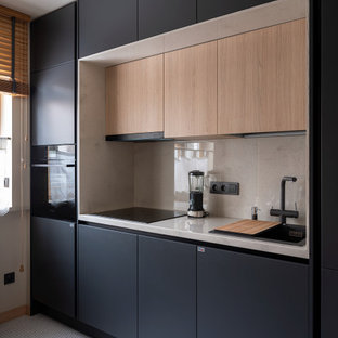 Diseño de cocina lineal, contemporánea, pequeña, sin isla, con fregadero encastrado, armarios con paneles lisos, puertas de armario negras, salpicadero beige, electrodomésticos con paneles y encimeras beige