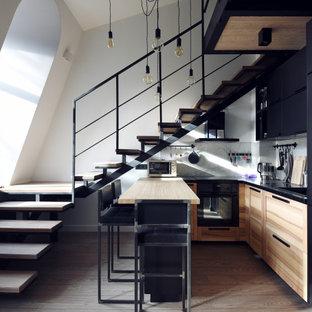 На фото: маленькая п-образная кухня в стиле лофт с монолитной раковиной, плоскими фасадами, светлыми деревянными фасадами, черной техникой, паркетным полом среднего тона, полуостровом, коричневым полом и бежевой столешницей с