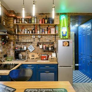 Стильный дизайн: маленькая угловая кухня-гостиная в стиле фьюжн с фасадами с филенкой типа жалюзи, синими фасадами, столешницей из дерева, фартуком из кирпича, пробковым полом, бежевым полом, коричневой столешницей, накладной раковиной и коричневым фартуком без острова - последний тренд