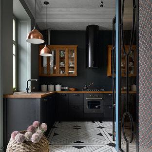 Geschlossene Moderne Küche ohne Insel in L-Form mit Einbauwaschbecken, flächenbündigen Schrankfronten, schwarzen Schränken, Arbeitsplatte aus Holz, Küchenrückwand in Schwarz, schwarzen Elektrogeräten, buntem Boden und brauner Arbeitsplatte in Moskau