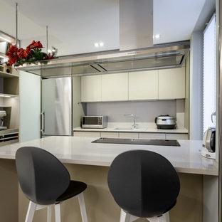 На фото: п-образная кухня в современном стиле с накладной раковиной, плоскими фасадами, бежевыми фасадами, техникой из нержавеющей стали, полуостровом и белой столешницей с