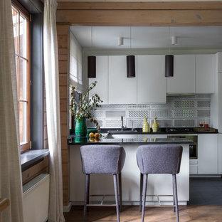 Идея дизайна: п-образная кухня среднего размера в современном стиле с обеденным столом, накладной раковиной, плоскими фасадами, белыми фасадами, столешницей из гранита, разноцветным фартуком, фартуком из керамической плитки, техникой из нержавеющей стали, полуостровом, черным полом и паркетным полом среднего тона