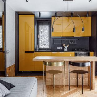 Diseño de cocina lineal, escandinava, pequeña, abierta, con armarios con paneles lisos, puertas de armario amarillas, salpicadero negro, electrodomésticos negros, suelo de madera en tonos medios, una isla, suelo marrón y encimeras negras