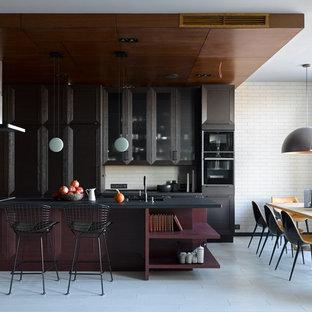 Свежая идея для дизайна: большая прямая кухня-гостиная в современном стиле с врезной раковиной, фасадами с утопленной филенкой, черными фасадами, белым фартуком, черной техникой, островом, белым полом и черной столешницей - отличное фото интерьера
