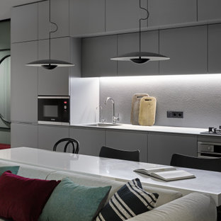 Inspiration for a medium sized contemporary single-wall kitchen/diner with a submerged sink, flat-panel cabinets, grey cabinets, engineered stone countertops, grey splashback, stainless steel appliances, terrazzo flooring, grey floors and grey worktops.