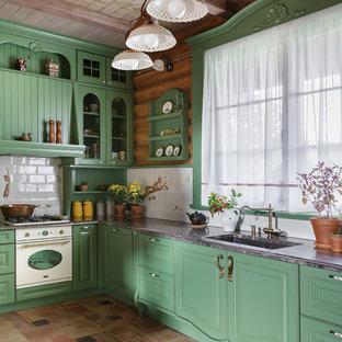 На фото: кухня в стиле кантри с врезной раковиной, фасадами с выступающей филенкой, зелеными фасадами, белым фартуком, белой техникой, коричневым полом и черной столешницей без острова с