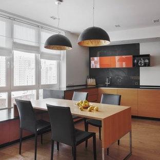 На фото: со средним бюджетом угловые кухни среднего размера в современном стиле с обеденным столом, плоскими фасадами, столешницей из акрилового камня, полом из ламината, черной столешницей, оранжевыми фасадами и черным фартуком