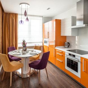 Стильный дизайн: маленькая линейная кухня в современном стиле с белым фартуком, фартуком из стекла, белой техникой, полом из винила, коричневым полом, плоскими фасадами, оранжевыми фасадами и обеденным столом без острова - последний тренд