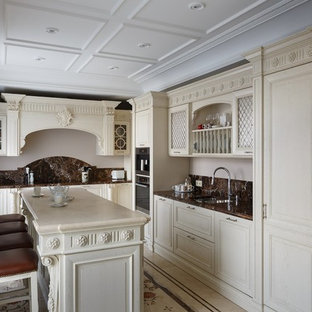 Traditional kitchen in Moscow with a double-bowl sink, raised-panel cabinets, beige cabinets, brown splashback, stainless steel appliances and with island.