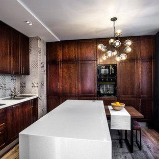 Удачное сочетание для дизайна помещения: угловая кухня-гостиная в современном стиле с двойной раковиной, фасадами в стиле шейкер, темными деревянными фасадами, серым фартуком, черной техникой, темным паркетным полом, островом и коричневым полом - самое интересное для вас
