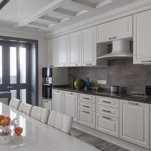 Свежая идея для дизайна: огромная линейная кухня в стиле современная классика с обеденным столом, врезной раковиной, белыми фасадами, столешницей из кварцита, фартуком из каменной плитки, полом из ламината, черной столешницей, фасадами с выступающей филенкой, серым фартуком, техникой из нержавеющей стали, островом, серым полом и кессонным потолком - отличное фото интерьера