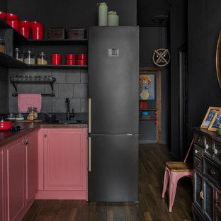 Idee per una cucina industriale di medie dimensioni con ante con bugna sagomata, top in legno, paraspruzzi nero, paraspruzzi in gres porcellanato, pavimento in laminato, nessuna isola, pavimento marrone, top marrone e lavello da incasso