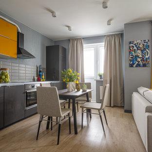 На фото: линейные кухни-гостиные в современном стиле с плоскими фасадами, желтыми фасадами, серым фартуком, техникой из нержавеющей стали, светлым паркетным полом и бежевым полом без острова