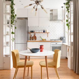 Пример оригинального дизайна: угловая кухня со шкафом над холодильником в скандинавском стиле с обеденным столом, накладной раковиной, плоскими фасадами, белыми фасадами, деревянной столешницей, белым фартуком, паркетным полом среднего тона, коричневым полом, коричневой столешницей и белой техникой без острова