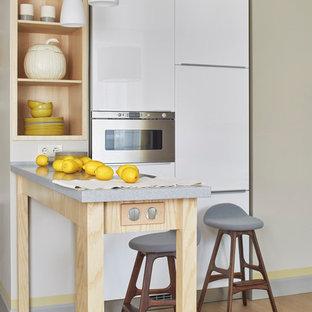 Свежая идея для дизайна: линейная кухня-гостиная в современном стиле с плоскими фасадами, белыми фасадами, техникой из нержавеющей стали и светлым паркетным полом - отличное фото интерьера