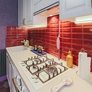 Geschlossene, Einzeilige, Kleine Klassische Küche ohne Insel mit integriertem Waschbecken, Schrankfronten mit vertiefter Füllung, beigen Schränken, Mineralwerkstoff-Arbeitsplatte, Küchenrückwand in Rot, Rückwand aus Metrofliesen, weißen Elektrogeräten, Porzellan-Bodenfliesen, rotem Boden und beiger Arbeitsplatte in Moskau
