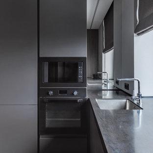 Идея дизайна: кухня в современном стиле с врезной раковиной, плоскими фасадами, серыми фасадами и черной столешницей