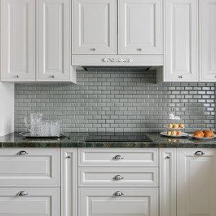 モスクワの小さいトラディショナルスタイルのおしゃれなキッチン (アンダーカウンターシンク、落し込みパネル扉のキャビネット、ベージュのキャビネット、御影石カウンター、緑のキッチンパネル、磁器タイルのキッチンパネル、シルバーの調理設備、磁器タイルの床、茶色い床、緑のキッチンカウンター) の写真