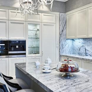 Новые идеи обустройства дома: кухня в стиле современная классика с врезной раковиной, фасадами с утопленной филенкой, белыми фасадами, серым фартуком и островом