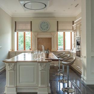 Источник вдохновения для домашнего уюта: угловая кухня в классическом стиле с бежевыми фасадами, бежевым фартуком, островом, коричневым полом и бежевой столешницей