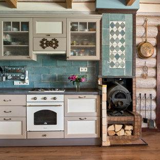 На фото: кухня в стиле кантри с фасадами в стиле шейкер, серыми фасадами, синим фартуком, паркетным полом среднего тона, коричневым полом и серой столешницей