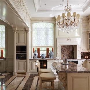 На фото: п-образная кухня в классическом стиле с белыми фасадами, коричневым фартуком, островом и коричневым полом
