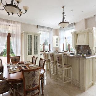 Неиссякаемый источник вдохновения для домашнего уюта: п-образная кухня в классическом стиле с обеденным столом, белыми фасадами, островом и бежевым полом