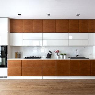 Свежая идея для дизайна: линейная кухня среднего размера в современном стиле с обеденным столом, накладной раковиной, плоскими фасадами, белыми фасадами, столешницей из акрилового камня, белым фартуком, фартуком из керамической плитки, черной техникой, паркетным полом среднего тона, коричневым полом и белой столешницей без острова - отличное фото интерьера