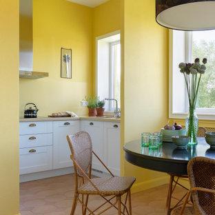 Пример оригинального дизайна: п-образная кухня в средиземноморском стиле с фасадами в стиле шейкер, белыми фасадами, желтым фартуком, коричневым полом, бежевой столешницей и врезной раковиной