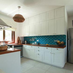 サンクトペテルブルクの地中海スタイルのおしゃれなキッチン (レイズドパネル扉のキャビネット、白いキャビネット、木材カウンター、グレーの床、オレンジのキッチンカウンター) の写真