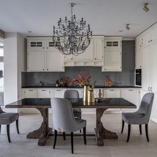 Идея дизайна: угловая кухня в стиле неоклассика (современная классика) с фасадами с утопленной филенкой, белыми фасадами, серым фартуком, черной техникой и серой столешницей без острова