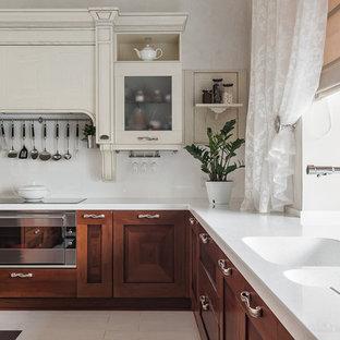 Создайте стильный интерьер: большая угловая кухня в классическом стиле с темными деревянными фасадами, столешницей из акрилового камня, белым фартуком, фартуком из каменной плиты, техникой из нержавеющей стали, полом из керамогранита, островом, белой столешницей, двойной раковиной и фасадами с утопленной филенкой - последний тренд