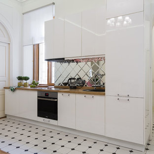 Mid-sized open concept kitchen designs - Example of a mid-sized single-wall cement tile floor and white floor open concept kitchen design in Saint Petersburg with a drop-in sink, flat-panel cabinets, white cabinets, wood countertops, mirror backsplash, stainless steel appliances and no island