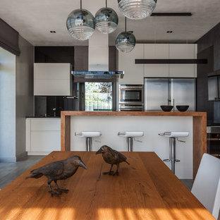 На фото: линейная кухня в современном стиле с обеденным столом, плоскими фасадами, белыми фасадами, серым фартуком, островом и серым полом с