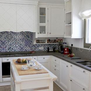 Пример оригинального дизайна: угловая кухня в средиземноморском стиле с фасадами с утопленной филенкой, белыми фасадами, синим фартуком, техникой из нержавеющей стали, островом и серой столешницей